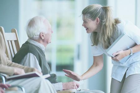 Pflegerin wendet sich älterem Herrn zu